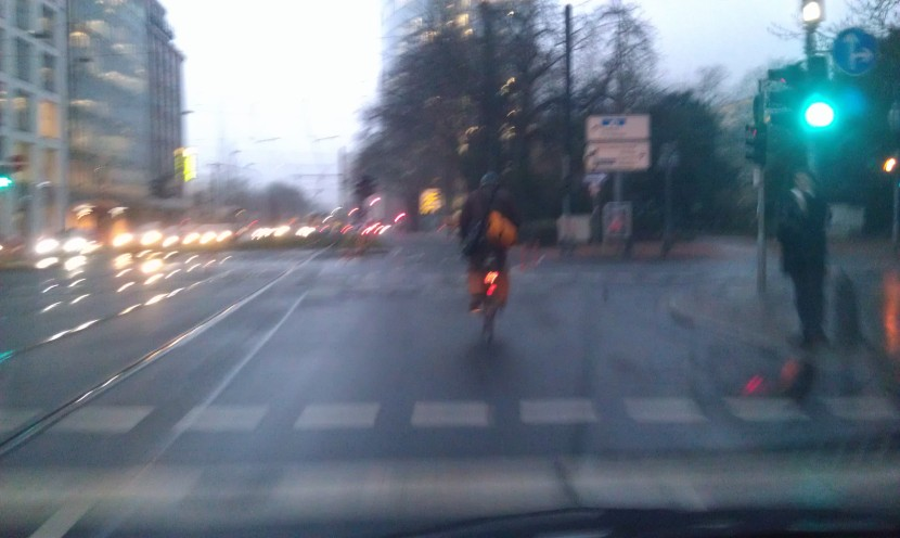 Ein Radler überquert die Kö. Dahinter beginnt der Radweg. Fast hat der Tollkühne es geschafft!
